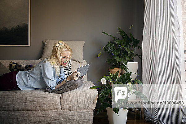 Happy woman using tablet computer while lying on sofa at home