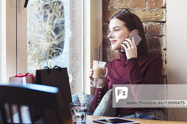 Woman with drink looking through window while talking on mobile phone in cafe