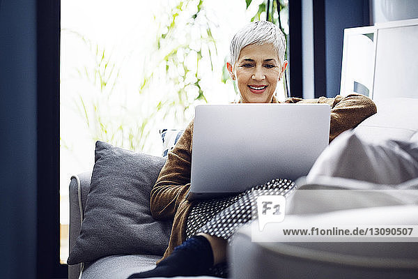 Smiling woman using laptop while sitting on sofa at home