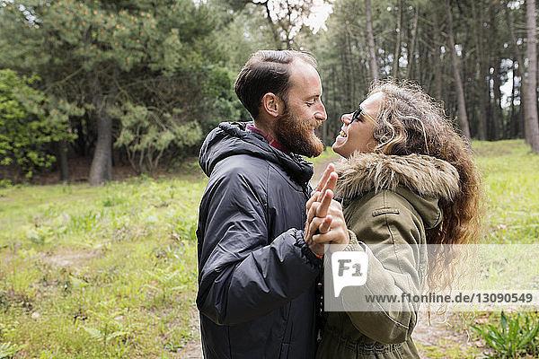 Seitenansicht eines glücklichen Liebespaares  das sich im Wald anschaut