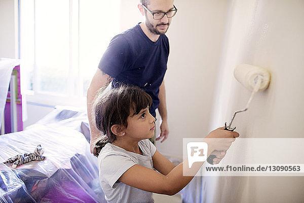 Vater führt Tochter zum Streichen der Wand im Haus