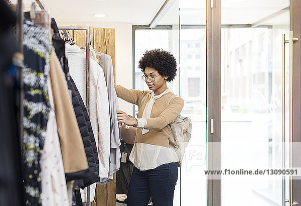Smiling woman choosing tops at clothes rack in shop on sunny day