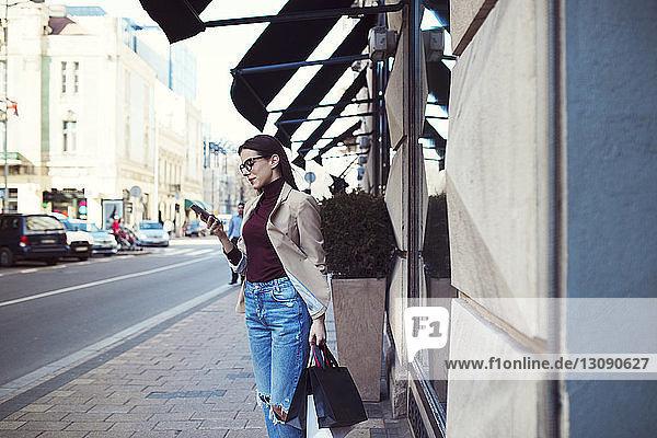 Frau mit Einkaufstaschen beim Telefonieren auf dem Bürgersteig in der Stadt