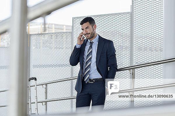 Selbstbewusster Geschäftsmann mit Smartphone in der U-Bahn-Station