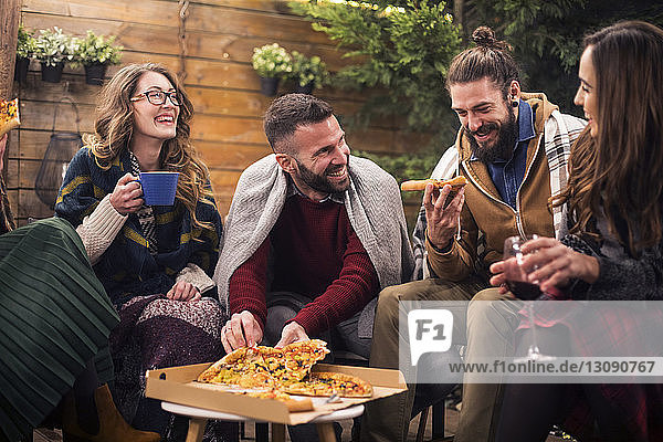 Glückliche Freunde essen abends Pizza im Hinterhof