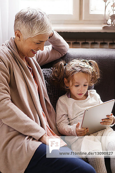 Girl using tablet computer while sitting by grandmother on sofa at home
