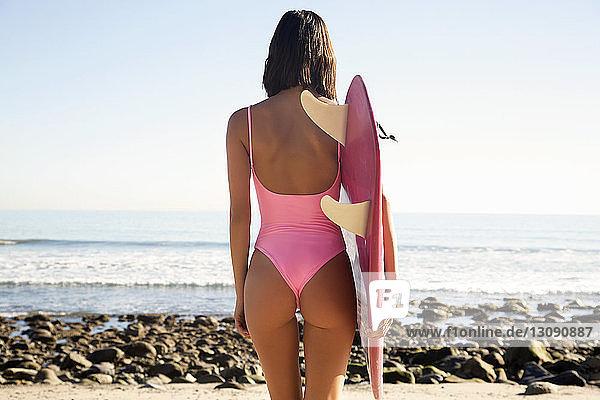 Rückansicht einer Frau mit Surfbrett  die am Strand am Ufer gegen den Himmel steht