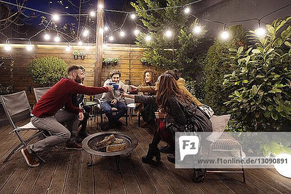 Fröhliche Freunde stoßen abends bei einer Party auf Getränke an