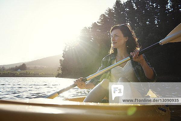 Smiling woman looking away while kayaking on lake during sunny day