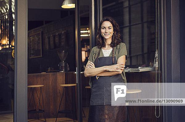 Porträt einer selbstbewussten Besitzerin mit verschränkten Armen vor dem Café