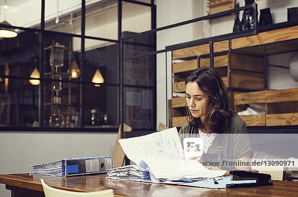 Reife Besitzerin analysiert Dokumente im Café