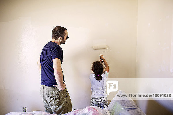 Mann sieht Tochter an  die eine Wand im Haus malt