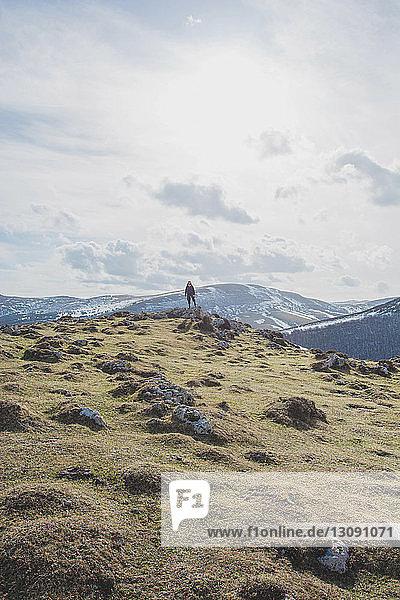 Mitteldistanzansicht eines Wanderers  der im Winter vor Bergen und bewölktem Himmel steht