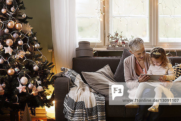 Grandmother assisting granddaughter using tablet computer while sitting on sofa