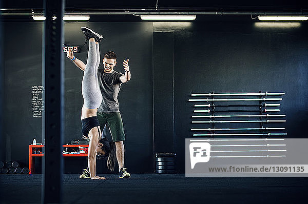 Fitness instructor assisting woman in doing handstand in gym
