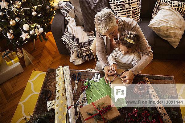 Draufsicht eines Mädchens und einer Großmutter  die zu Weihnachten ein Geschenk bei Tisch einpacken