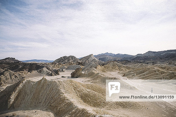 Mid distance view of hiker amidst desert against cloudy sky at Death Valley National Park