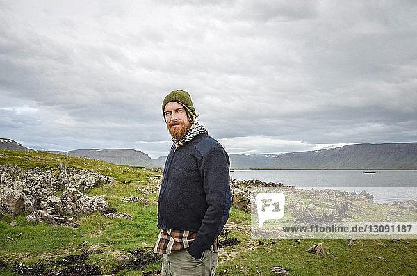 Porträt eines lächelnden Mannes  der auf einem Grasfeld am See vor bewölktem Himmel steht