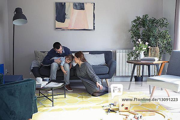 Glückliche Eltern spielen mit ihrem Sohn zu Hause