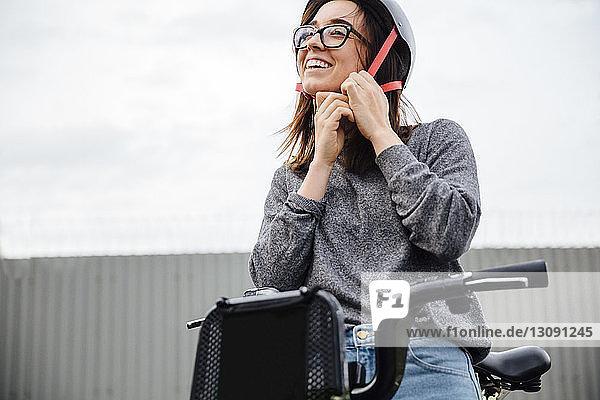 Niedriger Blickwinkel auf glückliche Frau mit Helm  die auf einem Citi Bike sitzt