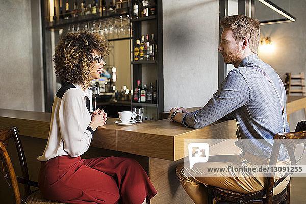 Glückliche Geschäftsfrau im Gespräch mit männlichem Kollegen an der Bar-Theke im Hotel