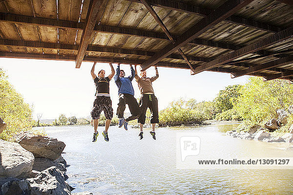 Friends exercising while hanging on bridge over river