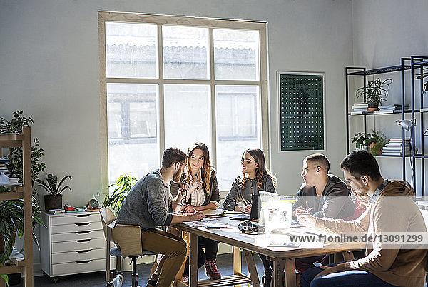 Lächelnde Freunde diskutieren  während sie im Klassenzimmer am Tisch sitzen