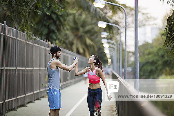 Smiling couple holding hands while jogging at park