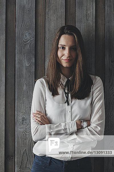 Porträt einer selbstbewussten Geschäftsfrau  die die Arme gegen eine Holzwand verschränkt