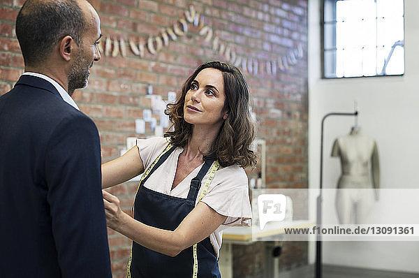 Modedesignerin im Gespräch mit einem Geschäftsmann bei der Maßabnahme im Workshop