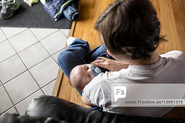 Hochwinkelaufnahme einer Mutter  die ihren Sohn hält  während sie zu Hause auf einem Parkettboden sitzt