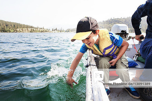 Happy son playing in water while traveling with father in motorboat on lake