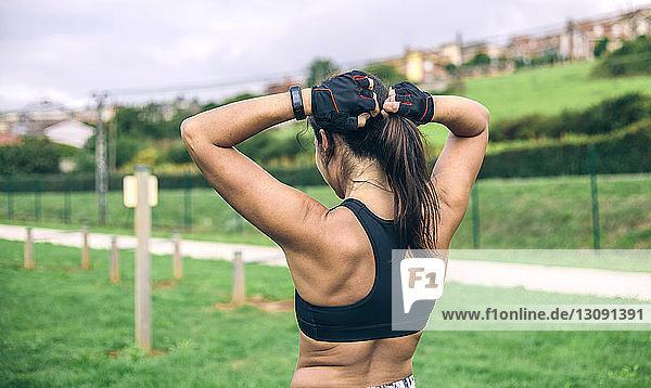 Rückansicht einer Frau  die einen Pferdeschwanz bindet  während sie im Park steht