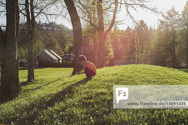 Side view of boy crouching on grassy field during sunny day