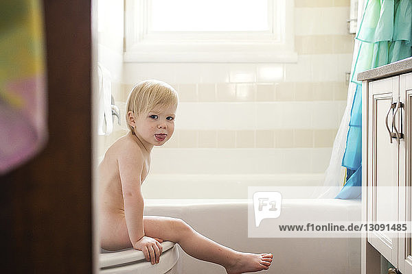Portrait of naked boy sitting on toilet at home
