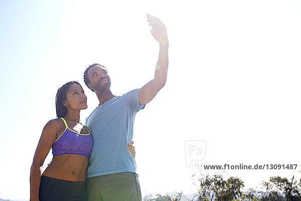 Niedrigwinkelansicht eines Paares  das sich bei klarem Himmel durch ein Mobiltelefon selbstständig macht