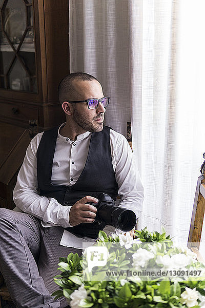 Thoughtful male photographer with camera sitting by window at home