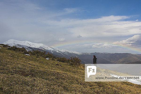 Wanderer steht im Winter gegen Berge und Regenbogen