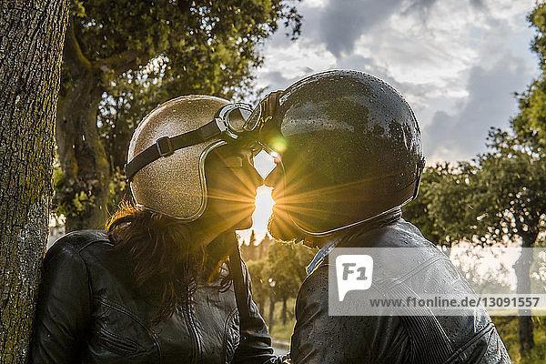 Romantisches Paar küsst sich bei Sonnenuntergang  während es am Himmel steht