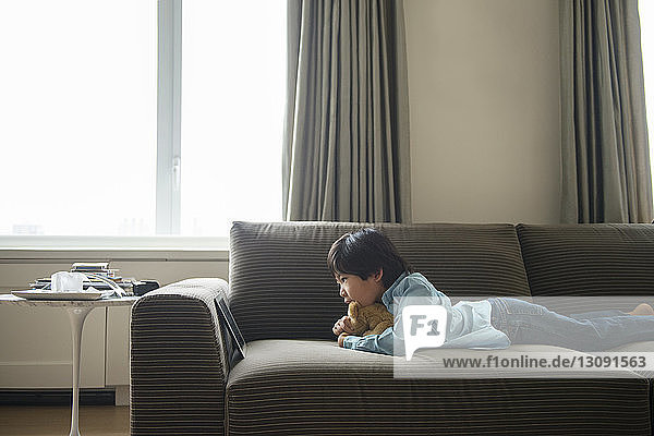 Boy looking at tablet while lying with stuffed toy on sofa at home