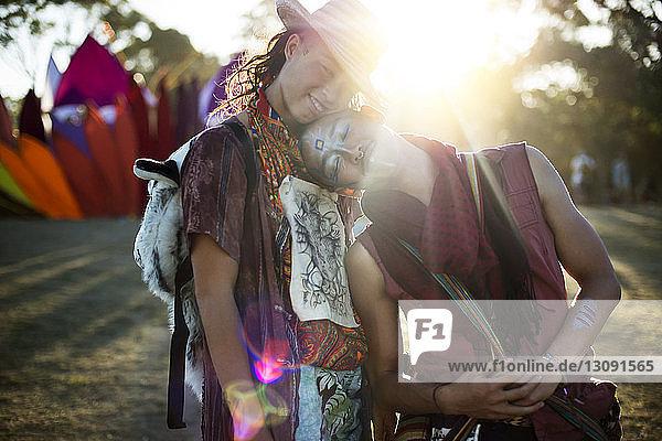 Lächelnde Freunde umarmen sich im Stehen bei einer traditionellen Veranstaltung