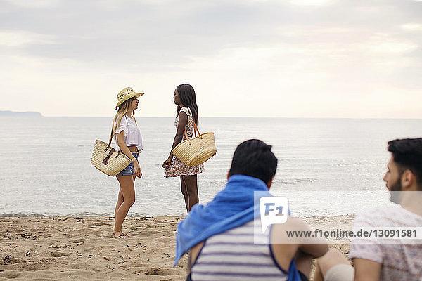 Männliche Freunde schauen Frauen an  die am Strand am Ufer stehen