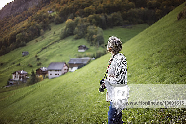 Woman holding camera while standing on hill