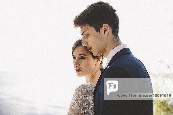 Hochzeitspaar steht am Strand gegen den Himmel