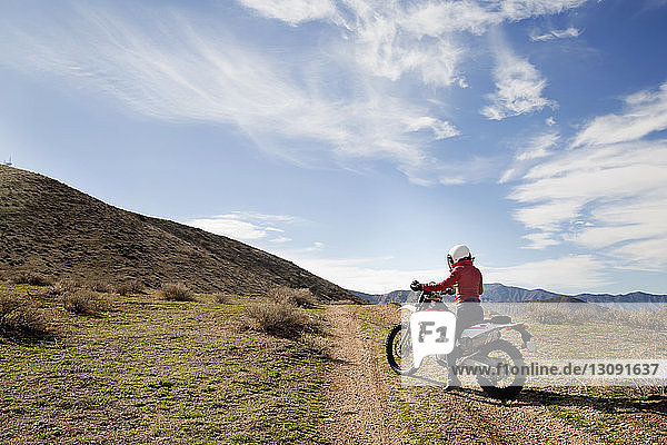 Seitenansicht einer Motorradfahrerin  die auf einem Motorrad auf dem Land sitzt