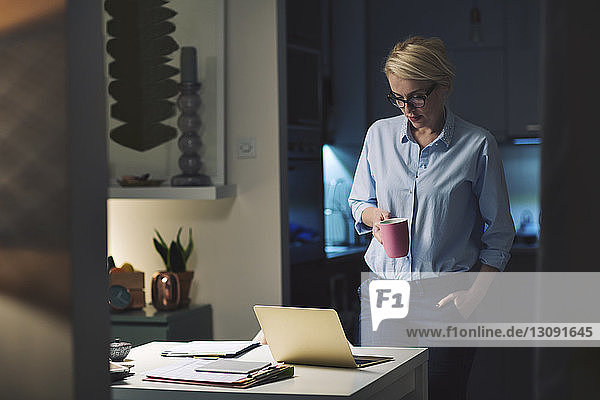 Businesswoman looking at laptop computer while standing in home office