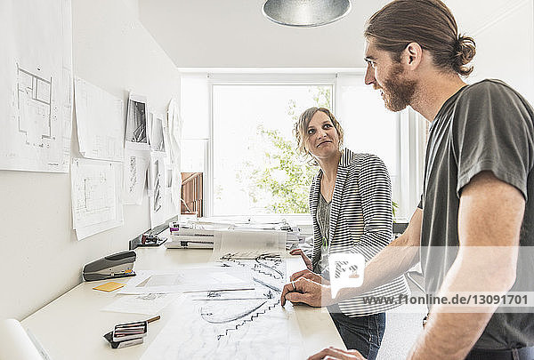 Professional man and woman discussing in office