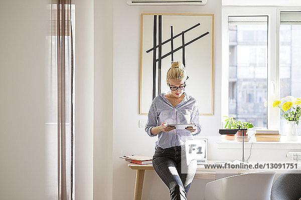Frau benutzt Tablet-Computer  während sie sich zu Hause an den Tisch lehnt