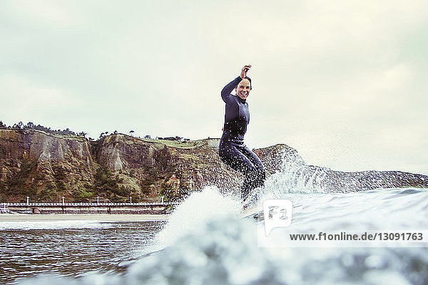 Portrait of happy woman surfing on sea against cloudy sky