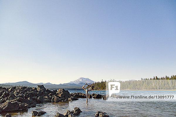 Frau steht auf einem Bein am Elk Lake vor klarem Himmel
